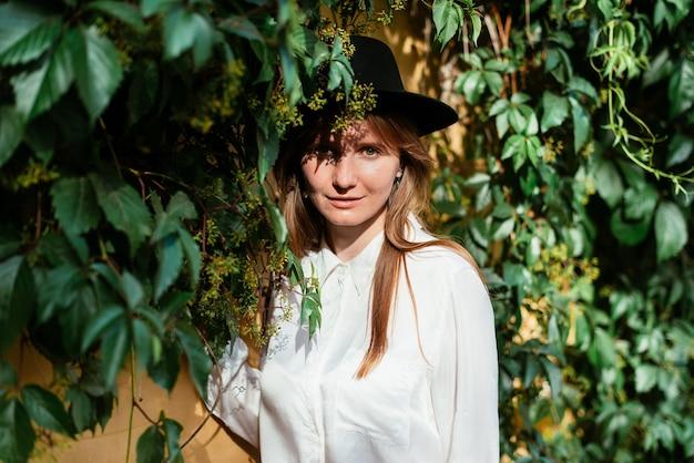 Mulher de chapéu olhando para a câmera perto do velho muro com folhas penduradas