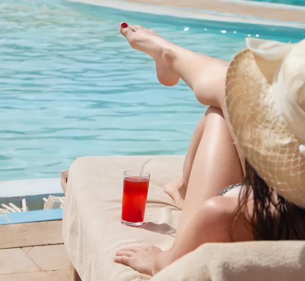 Mulher de chapéu relaxando à beira da piscina com um coquetel cosmopolita