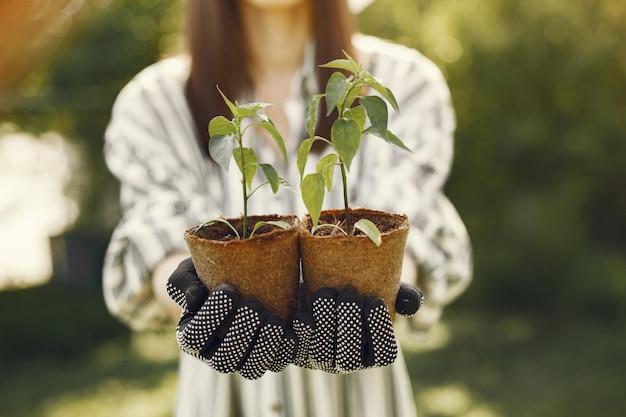 Mulher de chapéu segurando vasos de flores