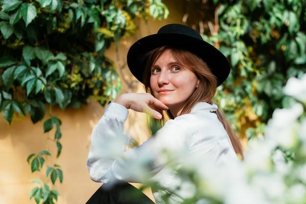 Mulher de chapéu sentada no fundo de um velho muro com folhas