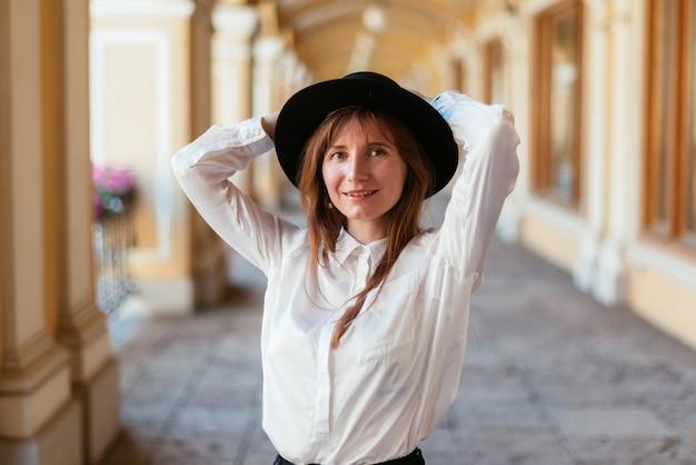 Mulher de chapéu sorri e anda pela cidade