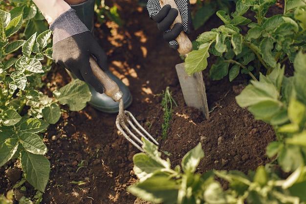 Mulher de chapéu trabalhando em um jardim