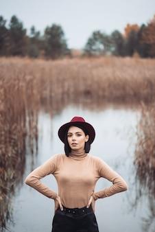 Mulher de chapéu vermelho, camiseta bege e calça preta andando na palha