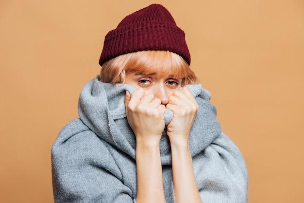Mulher de chapéu vermelho e lenço quente com olhos feridos e avermelhados sentindo os primeiros sintomas de gripe, olhando para a câmera