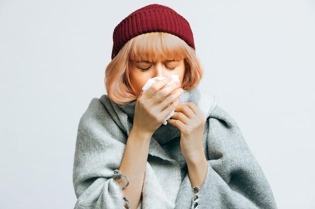 Mulher de chapéu vermelho espirra, experimenta sintomas de alergia