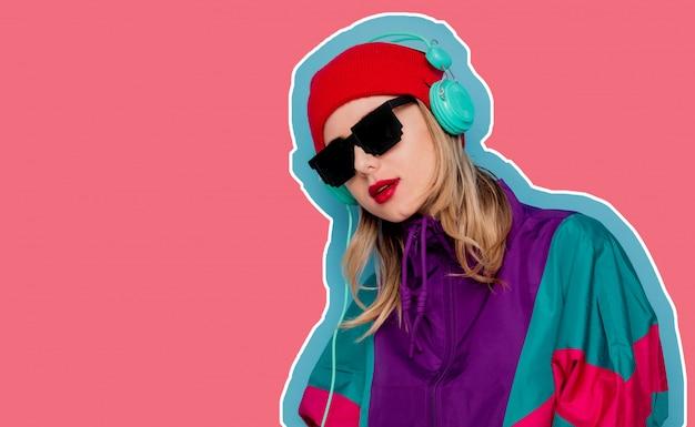 Mulher de chapéu vermelho, óculos escuros e terno dos anos 90 com fones de ouvido