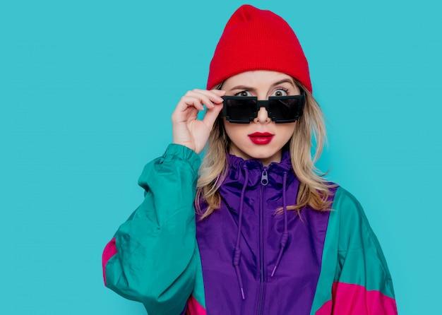 Mulher de chapéu vermelho, óculos escuros e terno dos anos 90