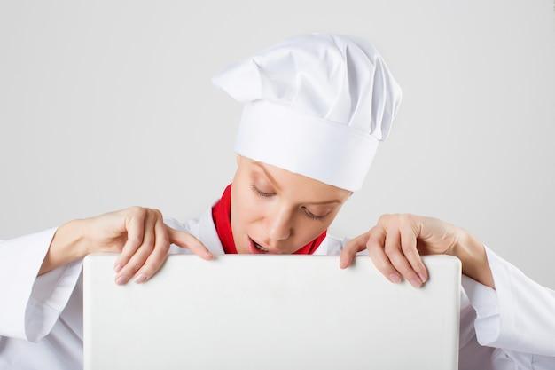 Mulher de chef ou padeiro, mostrando sinal de outdoor vazio em branco.