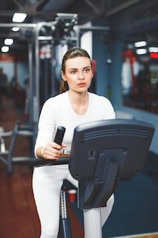 Mulher de ciclismo indoor fazendo cardio-treino biking na bicicleta de ginástica dentro de casa.