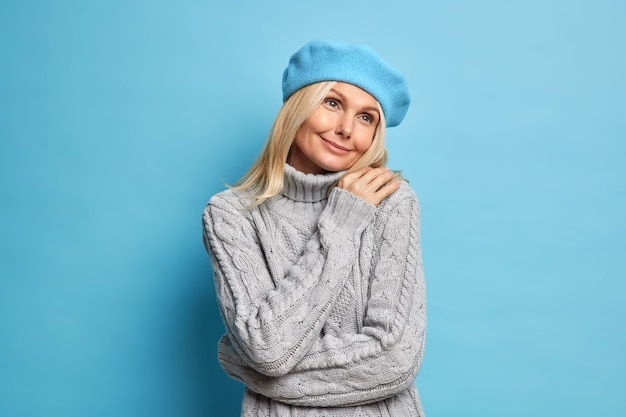Mulher de cinquenta anos encantadora e sonhadora se abraça, tem clima romântico, lembra de algo agradável, usa boina e suéter de tricô cinza