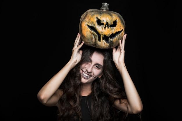 Mulher de cinza com abóbora de halloween acima da cabeça