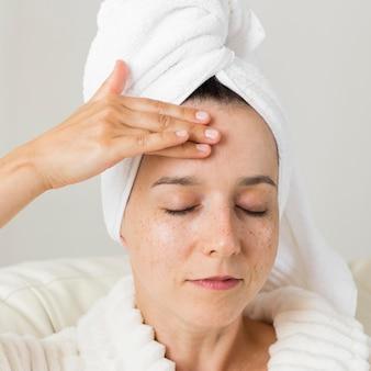 Mulher de close-up aplicando creme no rosto