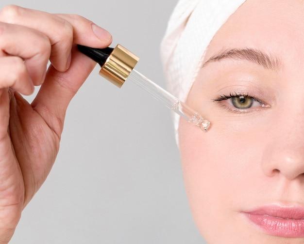 Mulher de close-up, aplicar soro facial