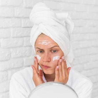 Mulher de close-up colocando máscara facial