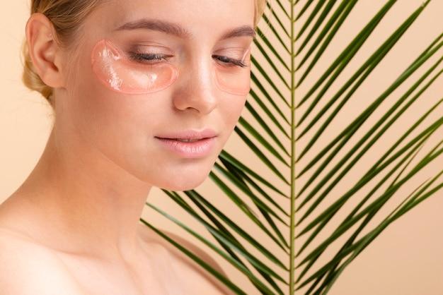 Mulher de close-up com almofadas para os olhos e folhas