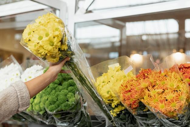 Mulher de close-up com buquê de flores amarelas