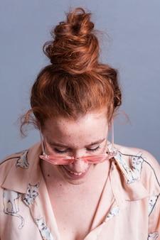 Mulher de close-up com cabelo bun e óculos cor de rosa