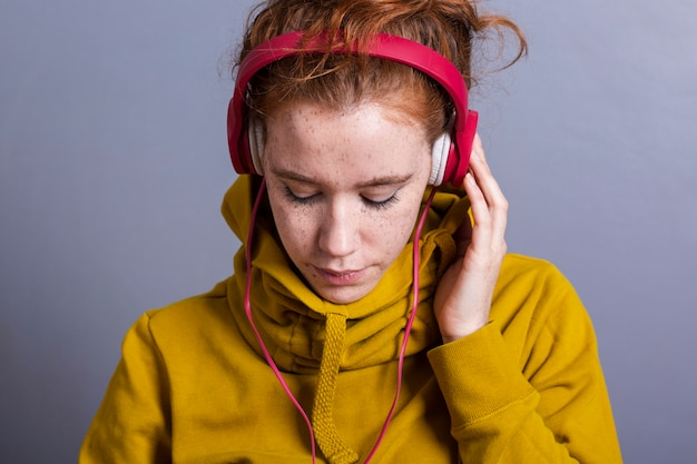 Mulher de close-up com capuz amarelo e fones de ouvido
