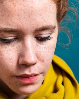 Mulher de close-up com características bonitas e capuz amarelo