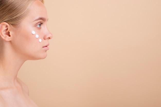 Mulher de close-up com creme para o rosto e cópia-espaço