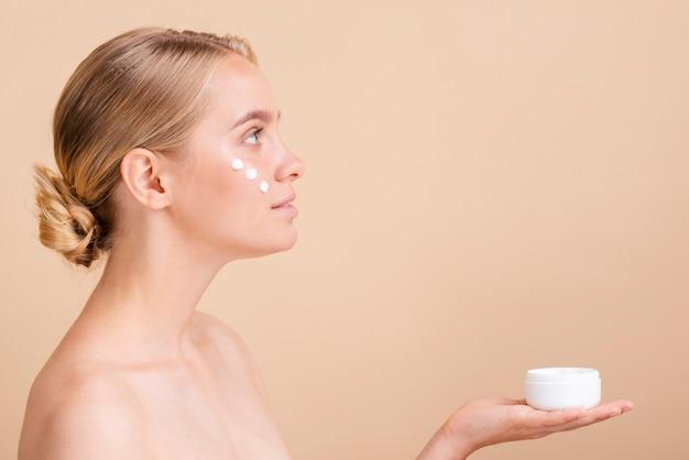 Mulher de close-up com creme para o rosto e jar