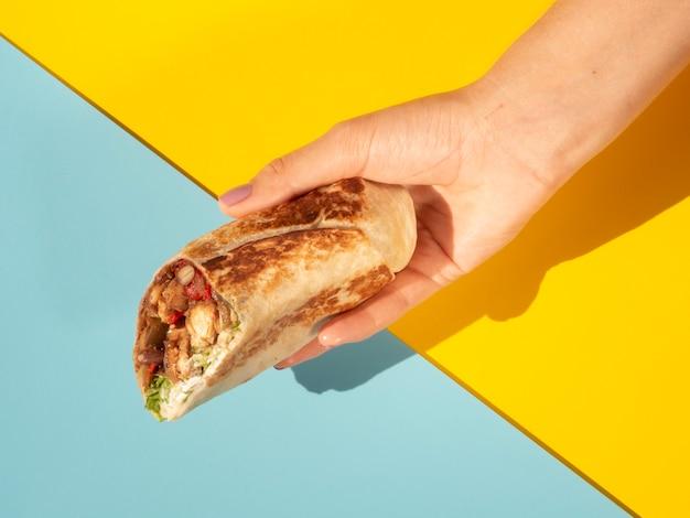 Mulher de close-up com delicioso burrito e fundo colorido