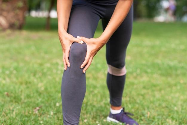 Mulher de close-up com dor no joelho