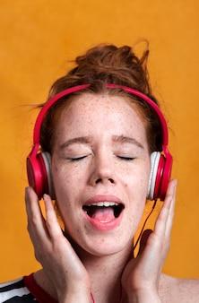 Mulher de close-up com fones de ouvido e boca aberta
