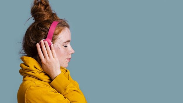 Mulher de close-up com fones de ouvido e cópia-espaço