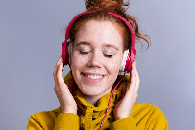 Mulher de close-up com fones de ouvido e sorriso largo