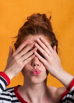 Mulher de close-up com fundo laranja, cobrindo o rosto