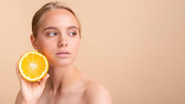 Mulher de close-up com laranja, olhando para longe