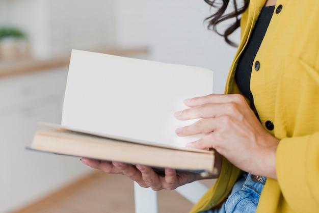 Mulher de close-up com livro dentro de casa