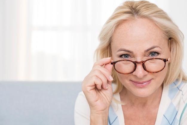 Mulher de close-up com óculos dentro de casa