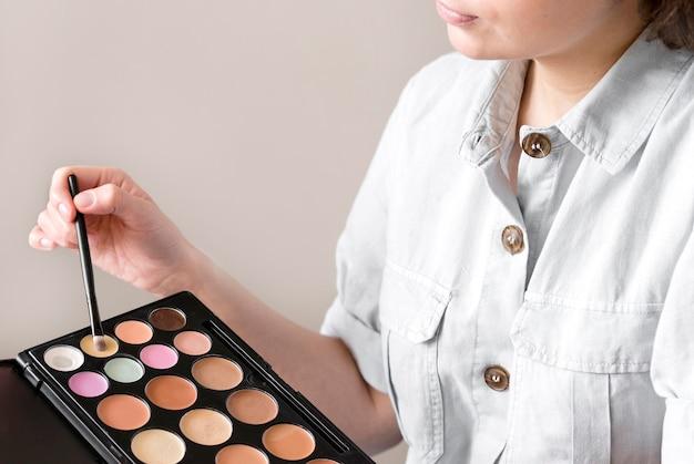 Mulher de close-up com paleta de sombra