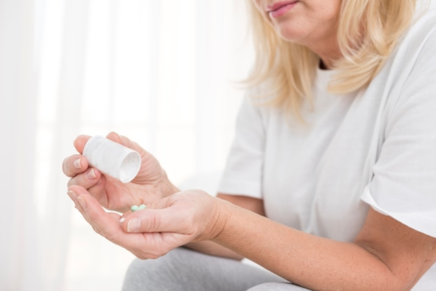 Mulher de close-up com pílulas no quarto