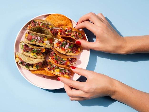 Mulher de close-up com prato cheio de tacos