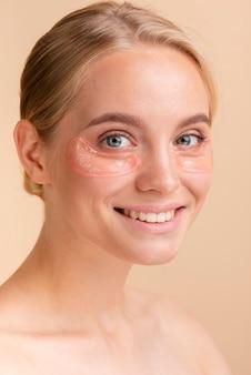 Mulher de close-up com sorriso largo e almofadas para os olhos