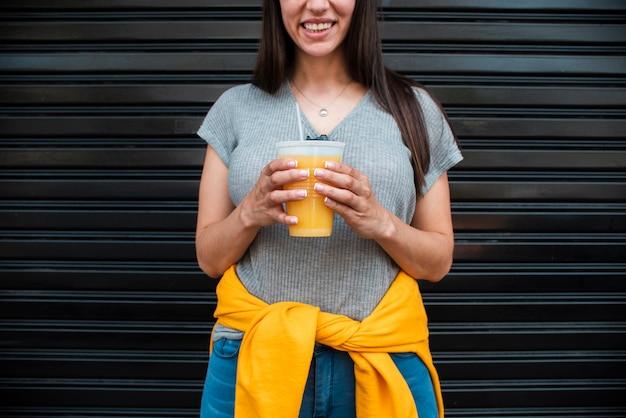 Mulher de close-up com suco de laranja