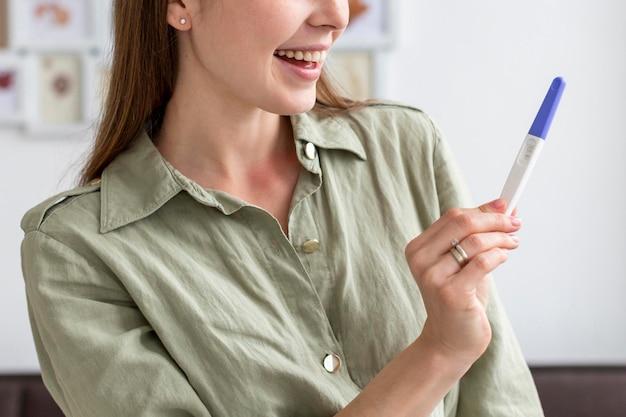 Mulher de close-up com teste de gravidez