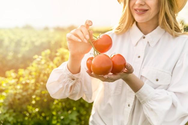Mulher de close-up com tomates