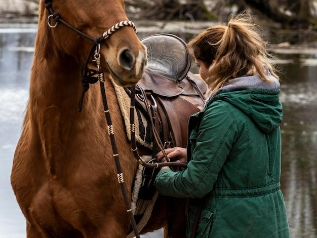 Mulher de close-up consertando a sela no cavalo