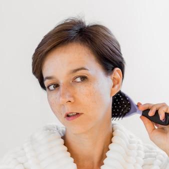 Mulher de close-up escovando o cabelo
