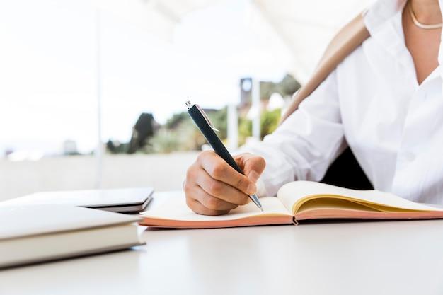 Mulher de close-up escrevendo no caderno