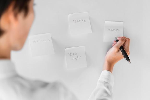 Mulher de close-up escrevendo nota auto-adesiva
