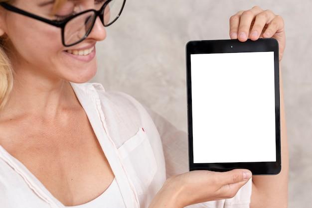 Mulher de close-up, mostrando um tablet com maquete