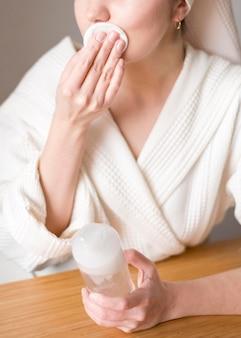 Mulher de close-up remover maquiagem