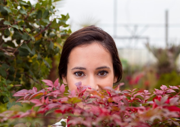 Mulher de close-up se escondendo atrás de plantas em estufa