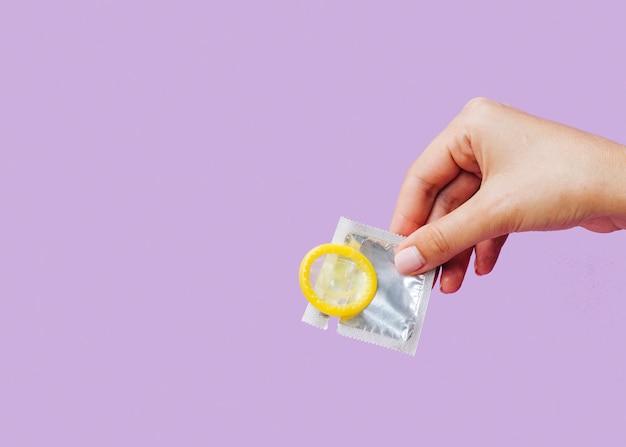 Mulher de close-up, segurando o preservativo com cópia-espaço