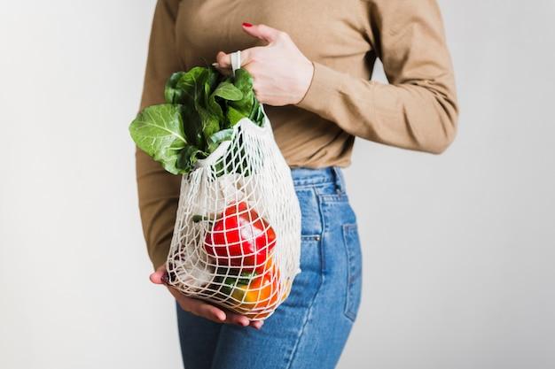 Mulher de close-up, segurando o saco de compras reutilizáveis